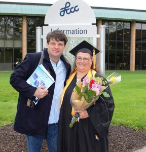 Donna, right, holds flowers while being congratulated by her husband following LCCC's 2016 Commencement ceremony.