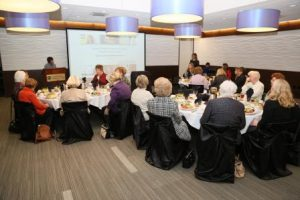 A room full of women sit at tables to listen to Jane Norton speak at the front of the room.