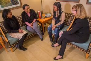 Four women talk while sitting on two couches.