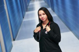 Dorisa Johnson wears medical scrubs and poses in a blue hallway.