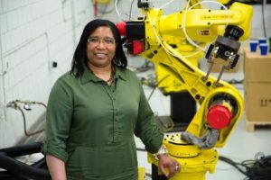 LePreece Thomas poses in green her work uniform by a large yellow machine.