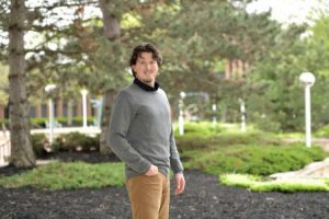 Nicholas Sutfin stands among green trees in the LCCC courtyard.