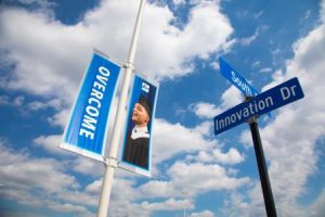 "A banner at Lorain County Community College reads, ""Overcome"" and a street sign says, ""Innovation Drive."""