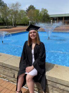 Sydney Contreras sits by the LCCC fountain, wearing her graduation cap and gown.